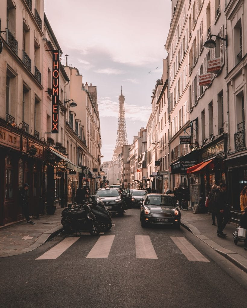 Image of a zebra crossing in Paris, with the Eiffel Tower in the background and traffic in the foreground.