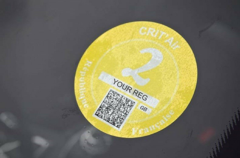 Image of a round yellow crit'air vignette (French 'clean air') sticker on a windscreen.